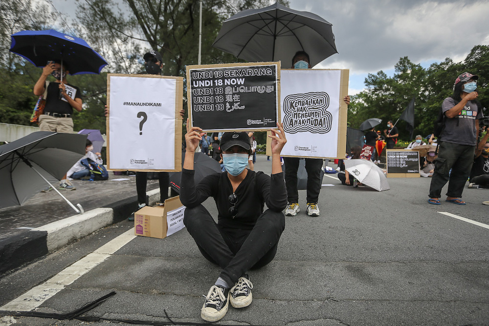 Protesters hold placards in front of Parliament building to protest the Election Commission's (EC) delay in allowing 18-years old to vote in Kuala Lumpur March 27, 2021. —Picture by Yusof Mat Isa