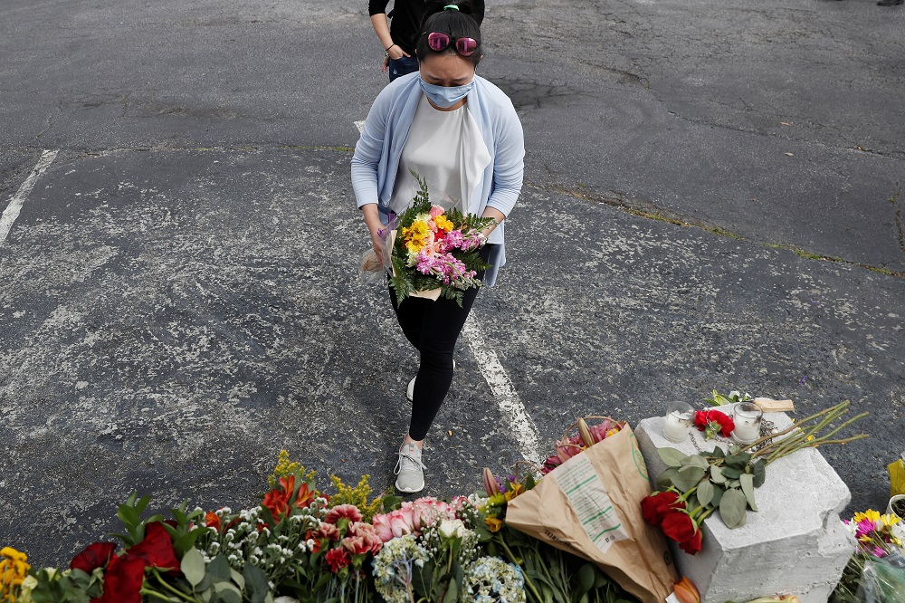 A woman lays flowers at a makeshift memorial outside the Gold Spa following the deadly shootings in Atlanta, Georgia March 19, 2021. ― Reuters pic