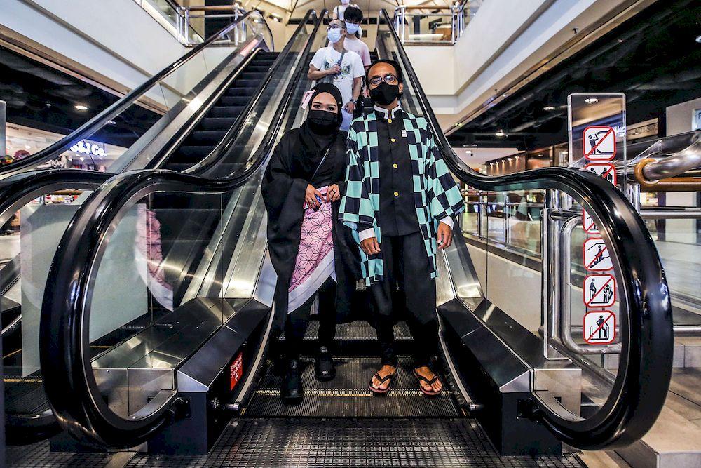 赫尔米(右起)与西蒂爱莎打扮成为《鬼灭之刃》男女角色去看电影。 -Hari Anggara摄-