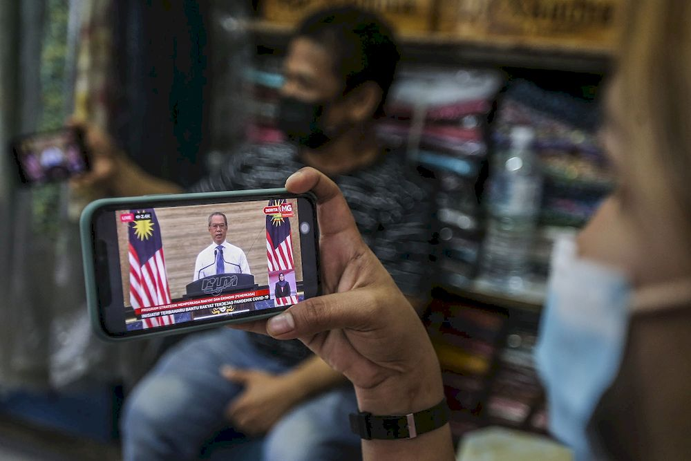 A store keeper at Jalan Tuanku Abdul Rahman watching the live telecast of Prime Minister Tan Sri Muhyiddin Yassin announcing the Pemerkasa programme in this file picture taken on March 17, 2021. ― Picture by Hari Anggara