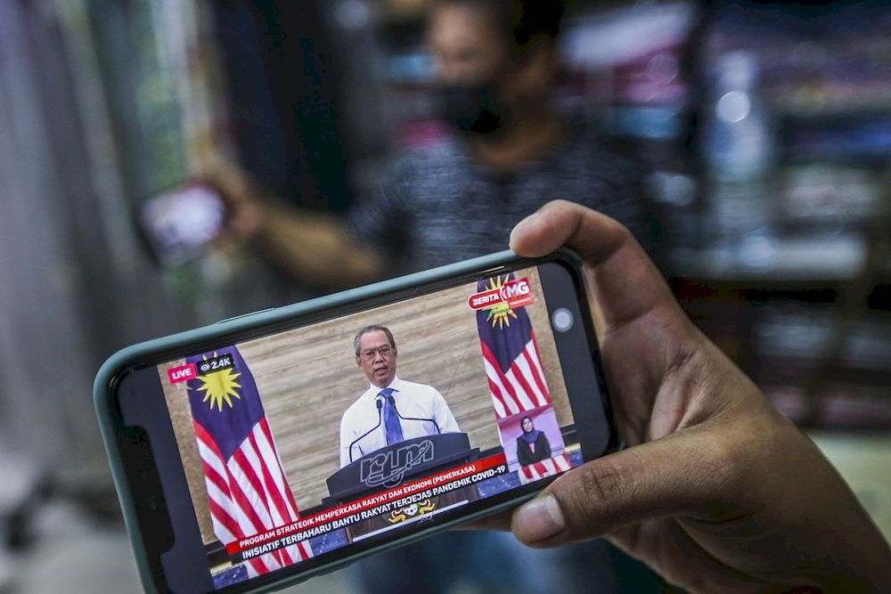 A store keeper in Jalan Tuanku Abdul Rahman watching the live telecast of Prime Minister Tan Sri Muhyiddin Yassin announcing the Pemerkasa (Strategic Programmes to Empower the People and Economy) economic recovery programme, March 17, 2021. ― Picture by Hari Anggara