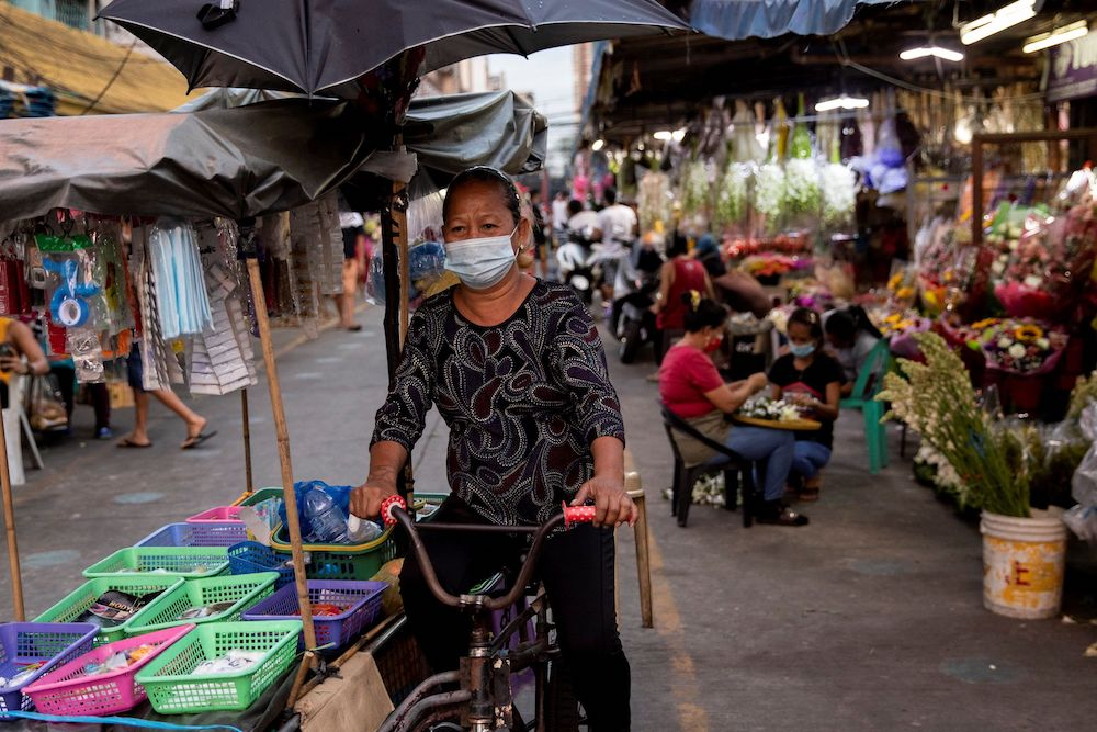 A vendor wearing a protective face mask, amid the spread of the coronavirus disease, cycles past a flower market in Manila, Philippines, March 12, 2021. — Reuters pic