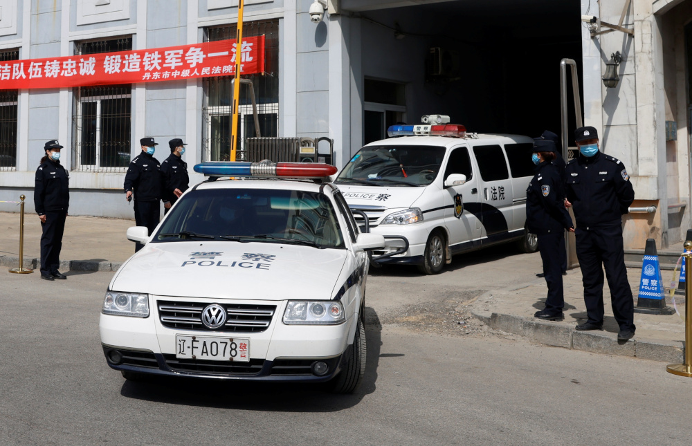 Police vehicles exit the Intermediate People's Court where Michael Spavor, a Canadian detained by China in December 2018 on suspicion of espionage, stood trial, in Dandong, Liaoning province, China March 19, 2021. — Reuters pic
