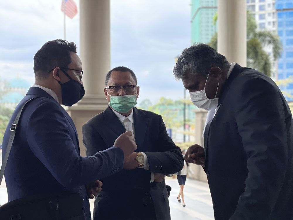 Datuk Mohd Puad Zarkashi (centre) speaks to his lawyers at the Kuala Lumpur High Court March 12, 2021. — Picture by Emmanuel Santa Maria Chin