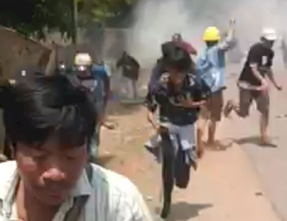 Protesters run away from live rounds in Naypyitaw, Myanmar March 20, 2021, in this still image from a social media video obtained by Reuters
