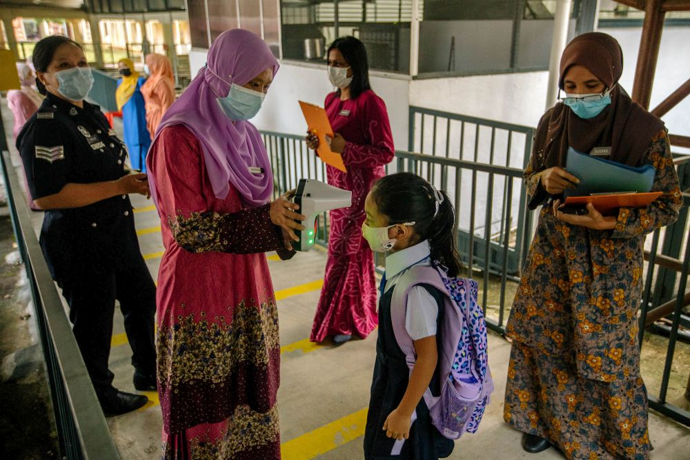 A Sekolah Kebangsaan Convent (2) Bukit Nanas student has her temperature checked on her first day back at school in Kuala Lumpur March 1, 2021. — Picture by Firdaus Latif