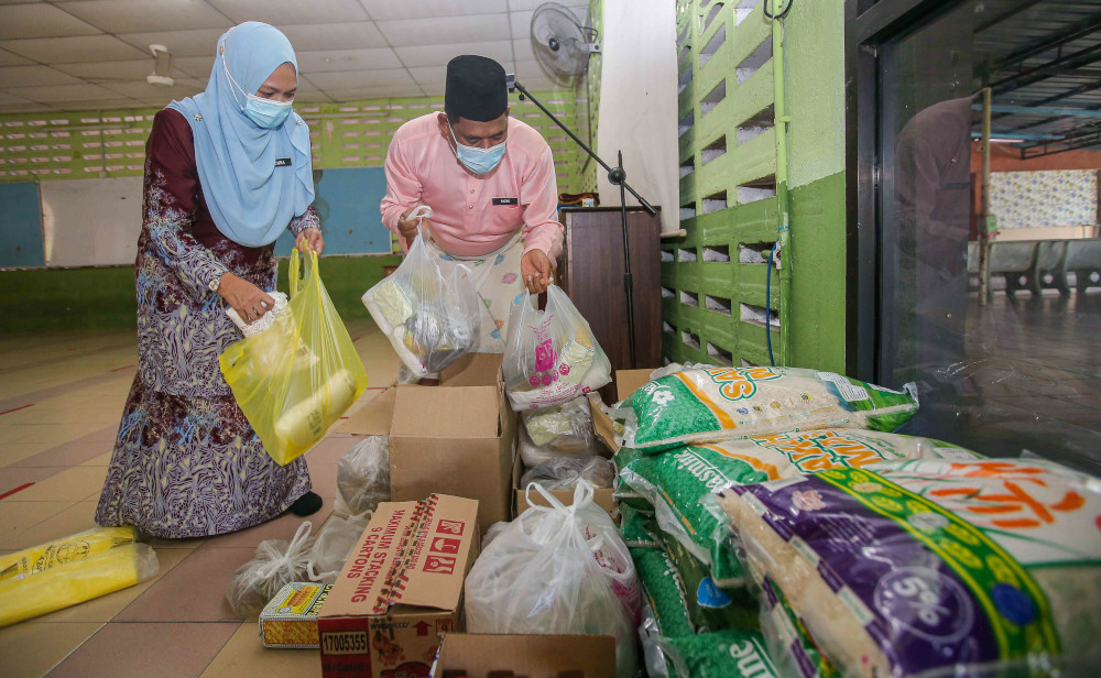Razak (right) and Adura Mohamed arranging items collected by the school for the needy students. — Picture by Farhan Najib