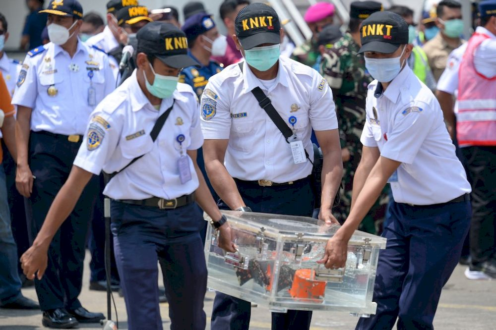 Indonesian officials carry a box contain cockpit voice recorder (CVR or blackbox) at the port in Tanjung Priok in Jakarta, on March 31, 2021, after it was recovered during search operations for the Sriwijaya Air Boeing 737-500 passenger jet which disappeared after taking off from Jakarta's international airport on January 9. — AFP pic