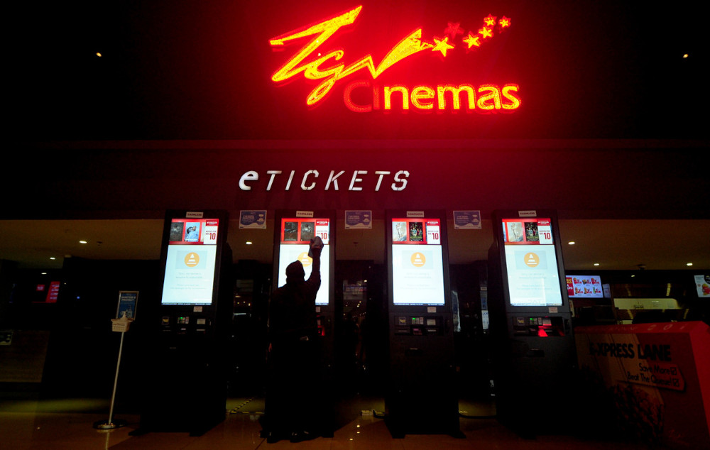 TGV Cinemas employee Maisura Mazhan, 29, cleaning the eTicket machine with disinfectant in preparation for the opening of the cinema at TGV Cinemas Bukit Tinggi Klang, March 4, 2021. — Bernama pic