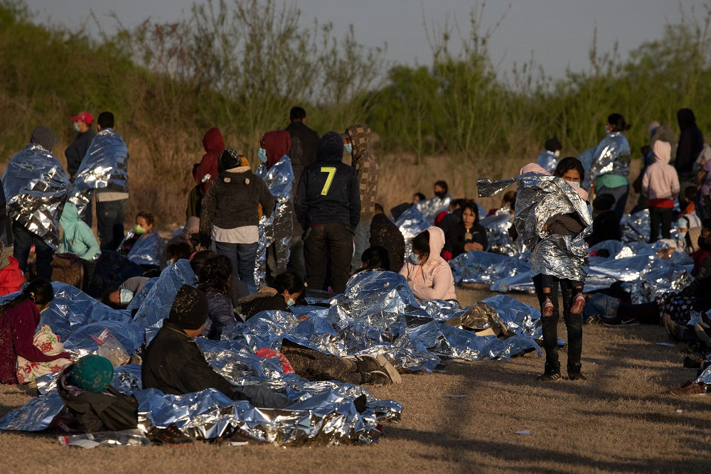 A group of asylum-seeking migrants from Central America take refuge near a baseball field after crossing the Rio Grande river into the United States from Mexico on rafts, in La Joya, Texas March 19, 2021. ― Reuters pic