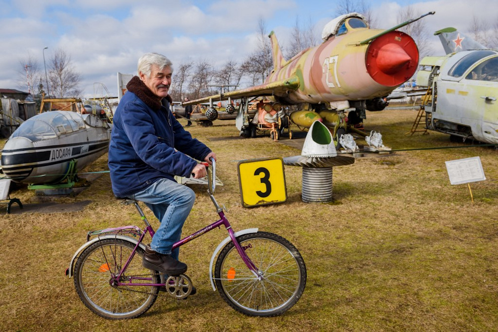 Museum owner Viktors Talpas rides a bicycle at his Aviation Museum in Riga on March 16, 2021. — AFP pic