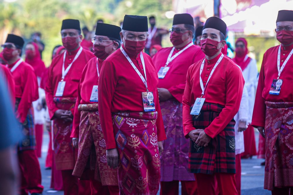 Umno president Datuk Seri Ahmad Zahid Hamidi (centre) arrives for the 2020 Umno general assembly in Kuala Lumpur March 28, 2021. — Picture by Shafwan Zaidon