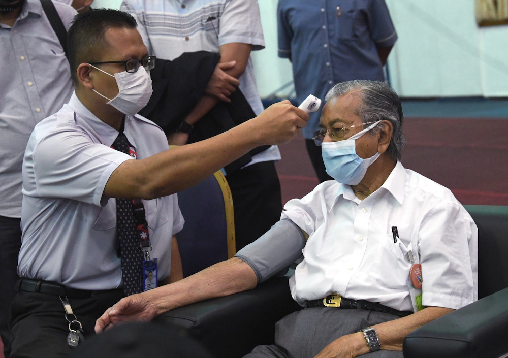Dr Mahathir gets his temperature tested after receiving the Covid-19 vaccine at the Vaccine Dispensing Centre at the Langkawi Sports Complex March 7, 2021. — Bernama pic