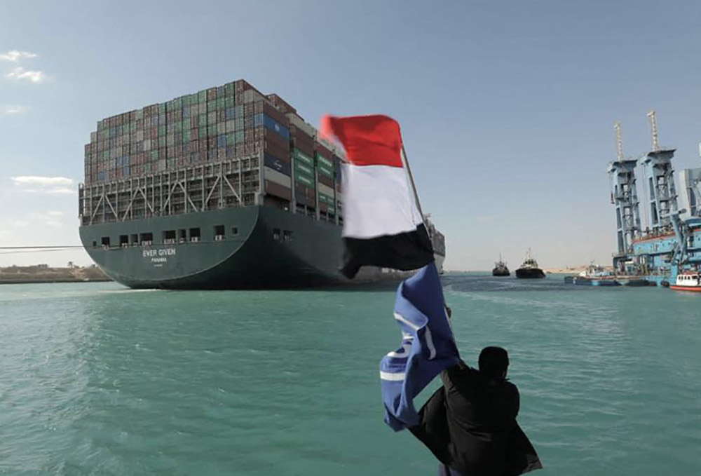 A man waving the Egyptian flag after Panama-flagged MV 'Ever Given' container ship was fully dislodged from the banks of the Suez, March 29, 2021. — Suez Canal Authority handout pic via AFP