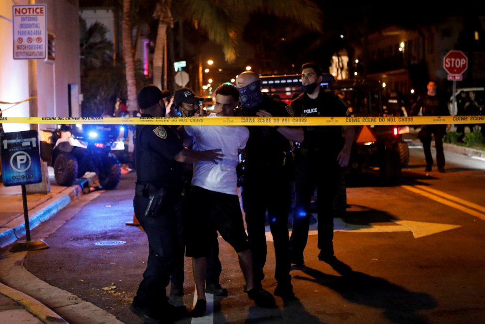 Police officers detain a man as they enforce an 8pm curfew imposed by local authorities on spring break festivities, amid the coronavirus pandemic, in Miami Beach, Florida, US, March 20, 2021. — Reuters pic