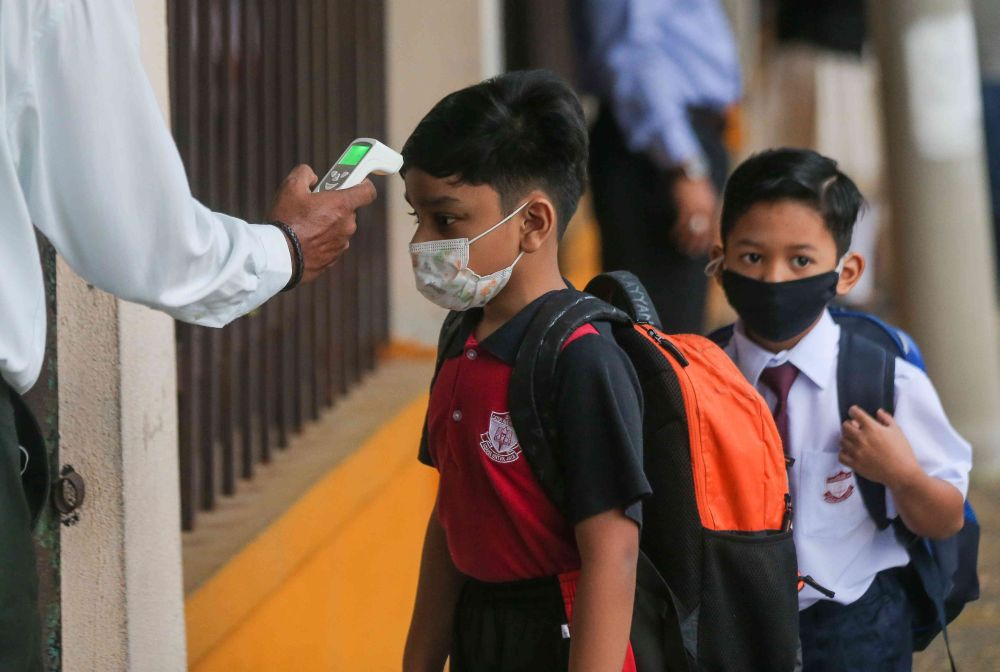 A student has his temperature checked at Sekolah Kebangsaan Cator Avenue, Ipoh as schools reopen March 1, 2021. — Picture by Farhan Najib