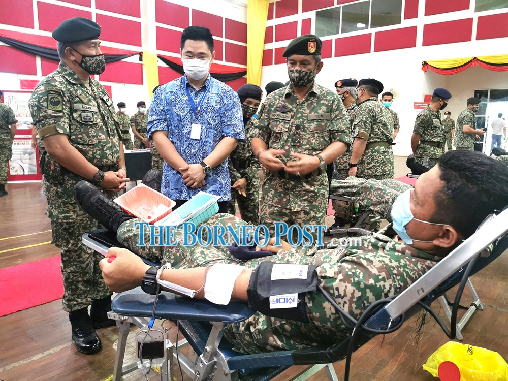 Mardzuki (standing, right) and Dr Wong on his right observe a soldier giving blood during the event. — Borneo Post Online pic