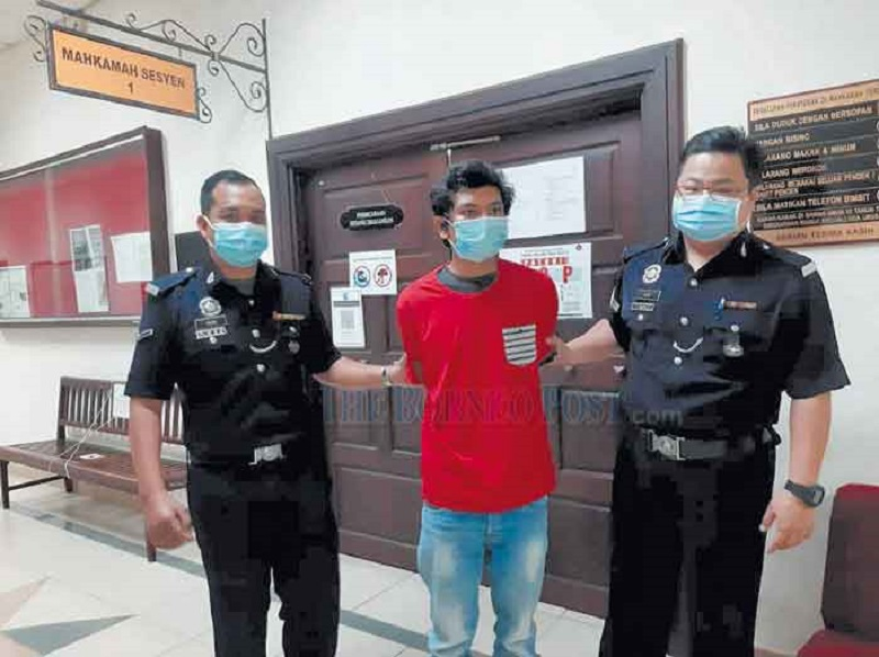 The accused is escorted out of the Sessions Court in Kuching March 5, 2021. — Borneo Post Online pic