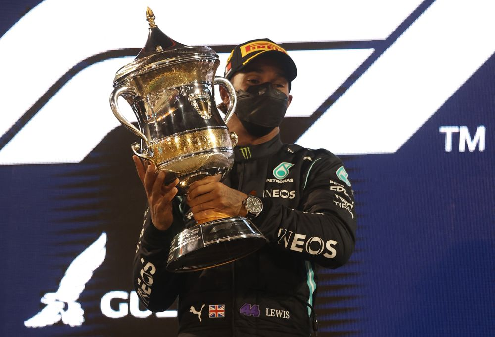 Mercedes' Lewis Hamilton celebrates winning the race on the podium with the trophy at the Bahrain International Circuit, Sakhir March 28, 2021. — Reuters pic