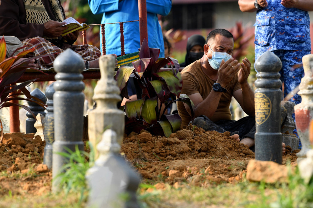 Liver donor Wan Mohd Hafizam Wan Ismail was seen escorting Mohd Afiq Ikmal Muhammad Zaini's remains from the hospital and assisted in the burial process in Tikam Batu, Kedah, March 2, 2021. — Bernama pic