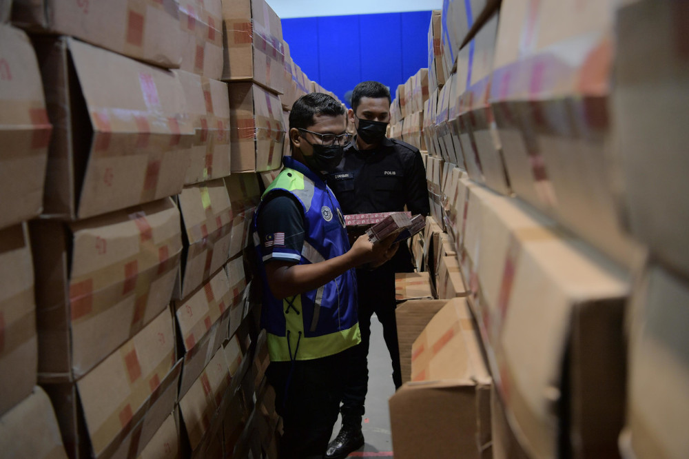 Police conduct checks on the smuggled cigarettes in Pontian, March 10, 2021. — Bernama pic