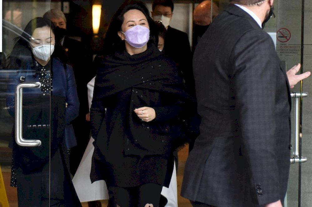 Huawei Chief Financial Officer, Meng Wanzhou (centre) leaves the British Columbia Supreme Court with her security detail in Vancouver, British Colombia, March 22, 2021. — AFP pic