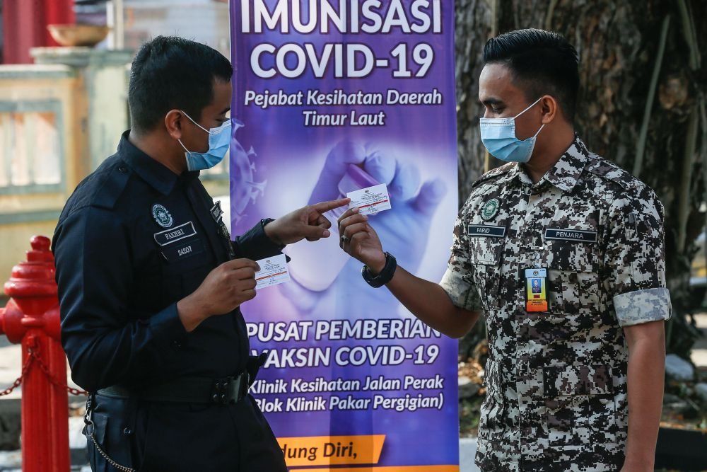 A Prisons Department personnel and a policeman hold up their vaccination cards after receiving their Covid-19 jabs at the Jalan Perak Health Clinic in Jelutong in this file picture taken on March 4, 2021. — Picture by Sayuti Zainudin