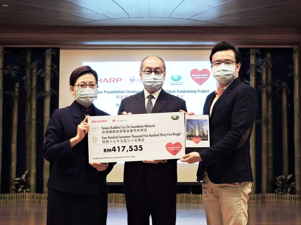 Chien (left) receiving the mock cheque from Ting (right) at the cheque presentation ceremony as Liu looks on. ― Picture courtesy of Sharp Malaysia