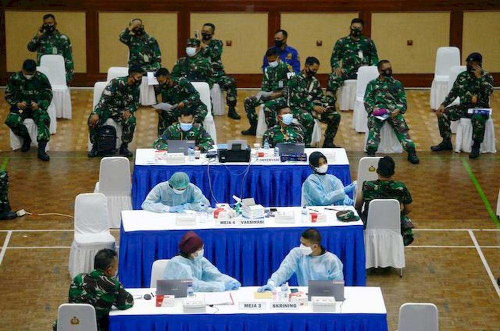 Indonesian soldiers sit as one of them receives a dose of China's Sinovac Biotech vaccine for the coronavirus disease (Covid-19), during a mass vaccination program at a sport hall in Jakarta, Indonesia, March 10, 2021. — Reuters pic