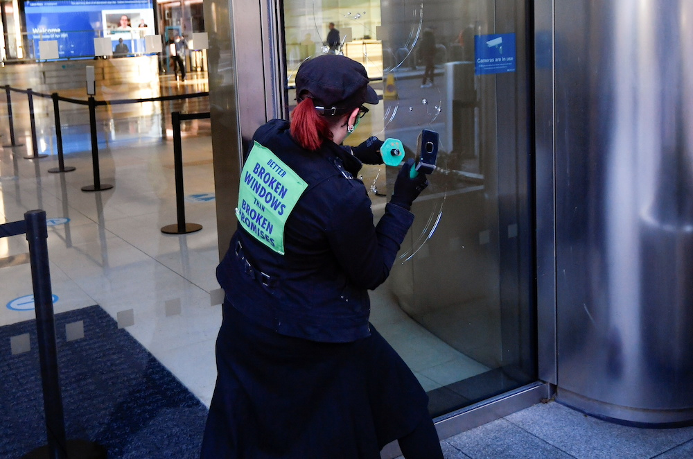 An activist from the Extinction Rebellion, a global environmental movement, damages a window during a direct action at Barclays offices in Canary Wharf, London April 7, 2021. — Reuters pic