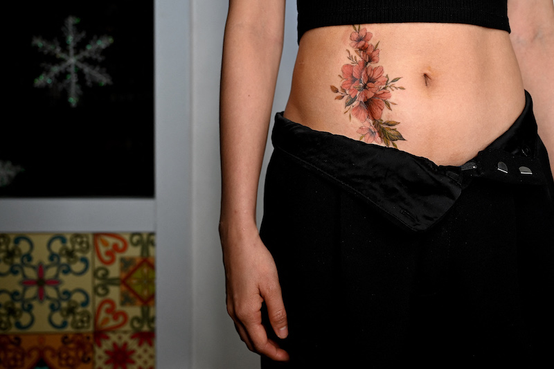 This photograph taken on March 20, 2021 shows a female customer posing with her new tattoo to cover her post-surgery scar at tattoo artist Ngoc Like's studio in Hanoi. — AFP pic