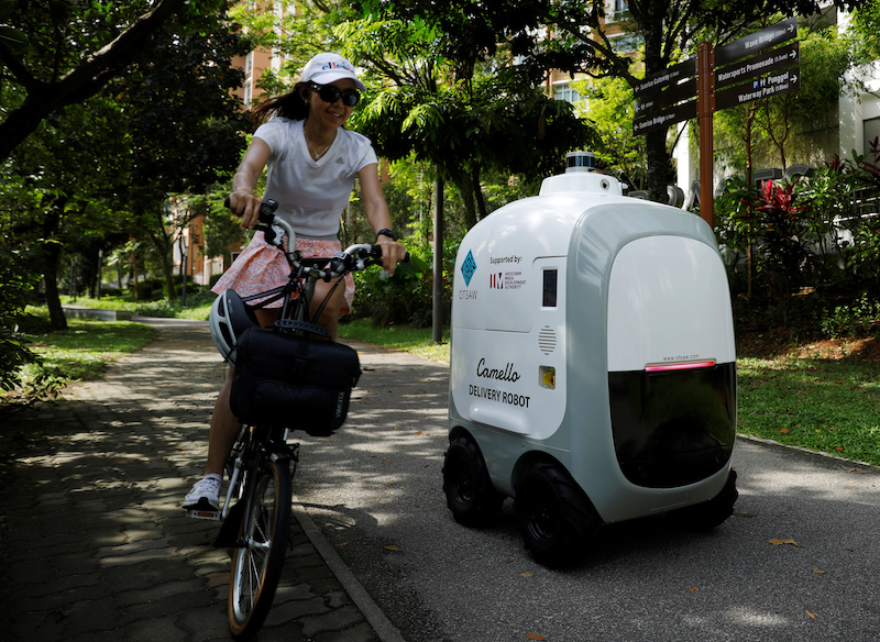 A cyclist passes as Carmello, an autonomous grocery delivery robot, makes its way during a delivery in Singapore April 6, 2021. — Reuters pic