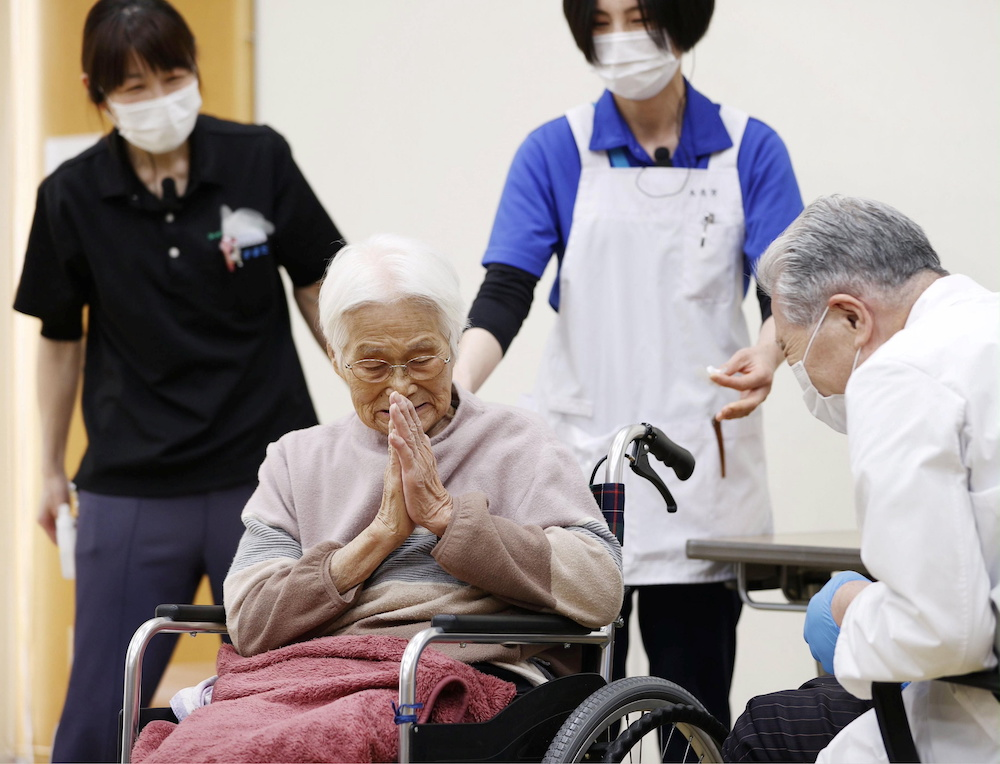 An elderly woman gestures to express gratitude after receiving a coronavirus disease (Covid-19) vaccination in Itami, western Japan April 12, 2021, in this photo released by Kyodo. — Kyodo/via Reuters