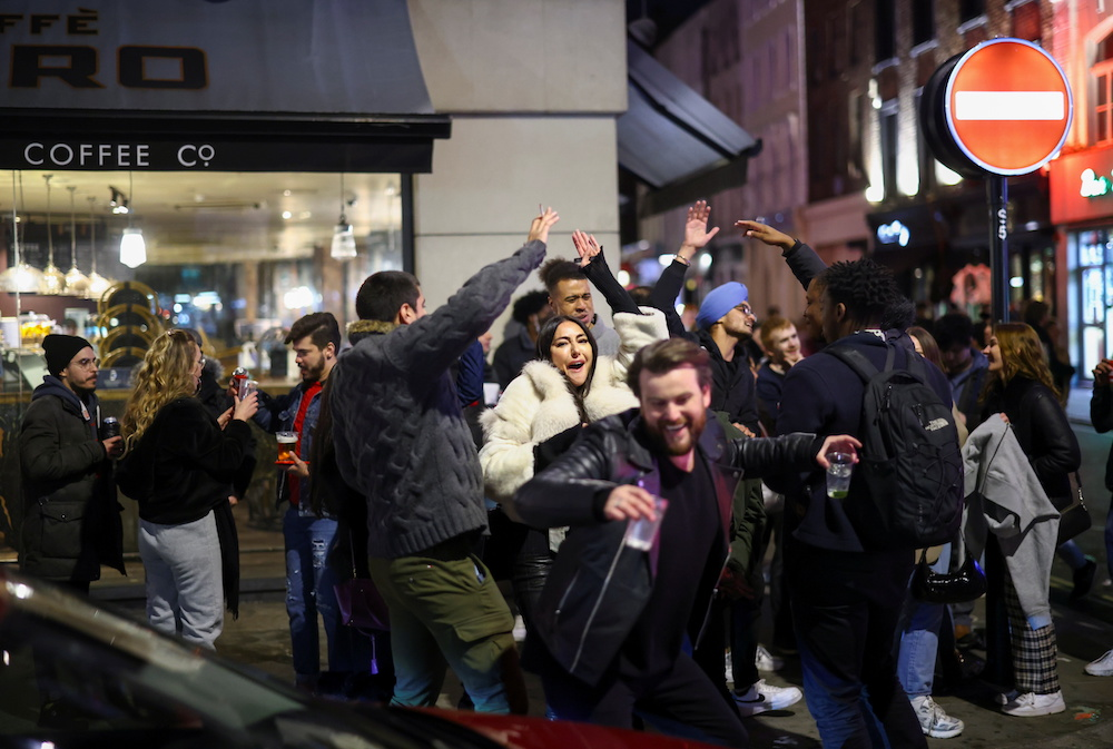 A group of people dance as they party on a street in Soho, as the coronavirus disease (Covid-19) restrictions ease, in London, Britain April 12, 2021. — Reuters pic