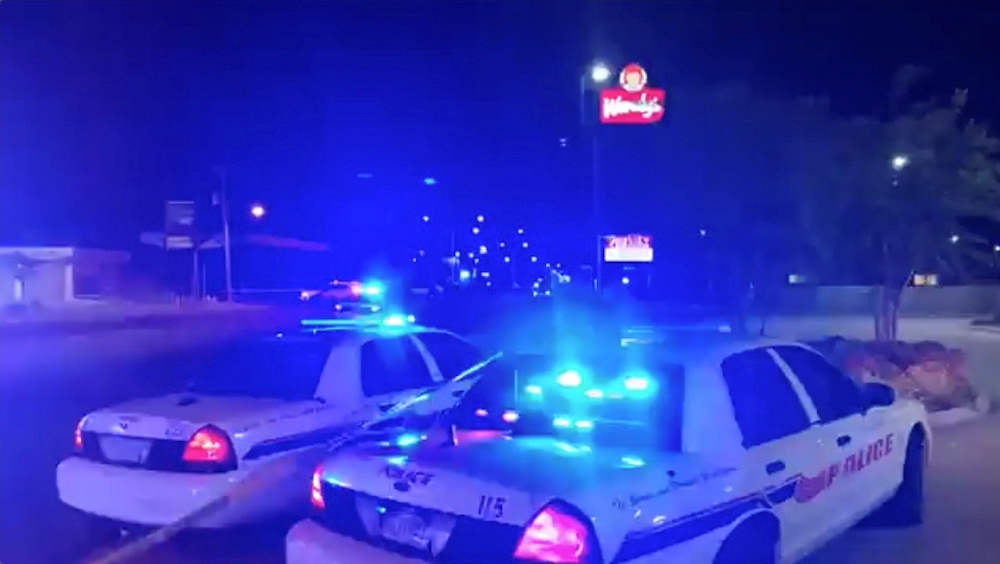 Police vehicles are seen near the scene in the aftermath of a drive-by shooting at a liquor store in Shreveport, Louisiana April 18, 2021, in this still image from video obtained via social media. — Love Shreveport-Bossier via Reuters
