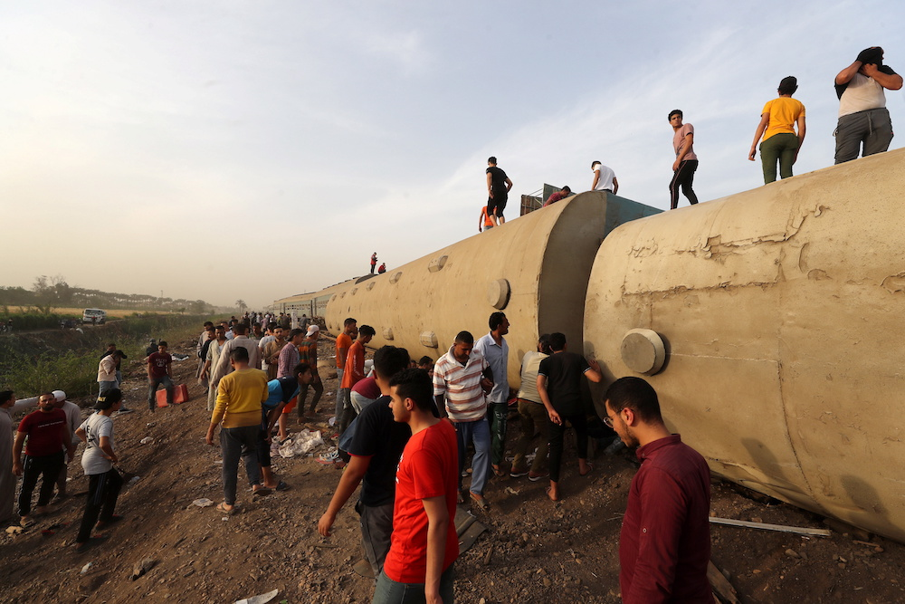 People gather at the site where train carriages derailed in Qalioubia province, north of Cairo, Egypt April 18, 2021. — Reuters pic