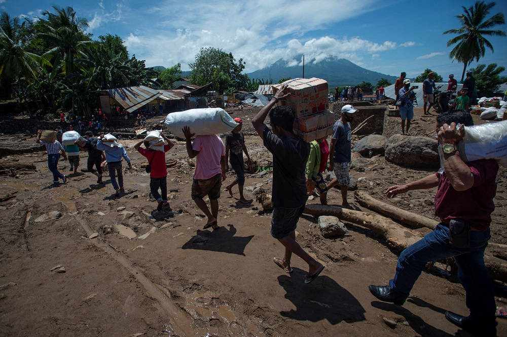 People carry relief supplies following flash floods triggered by tropical cyclone Seroja in East Flores, East Nusa Tenggara province, Indonesia April 7, 2021. — Picture by Aditya Pradana Putra/Antara Foto via Reuters