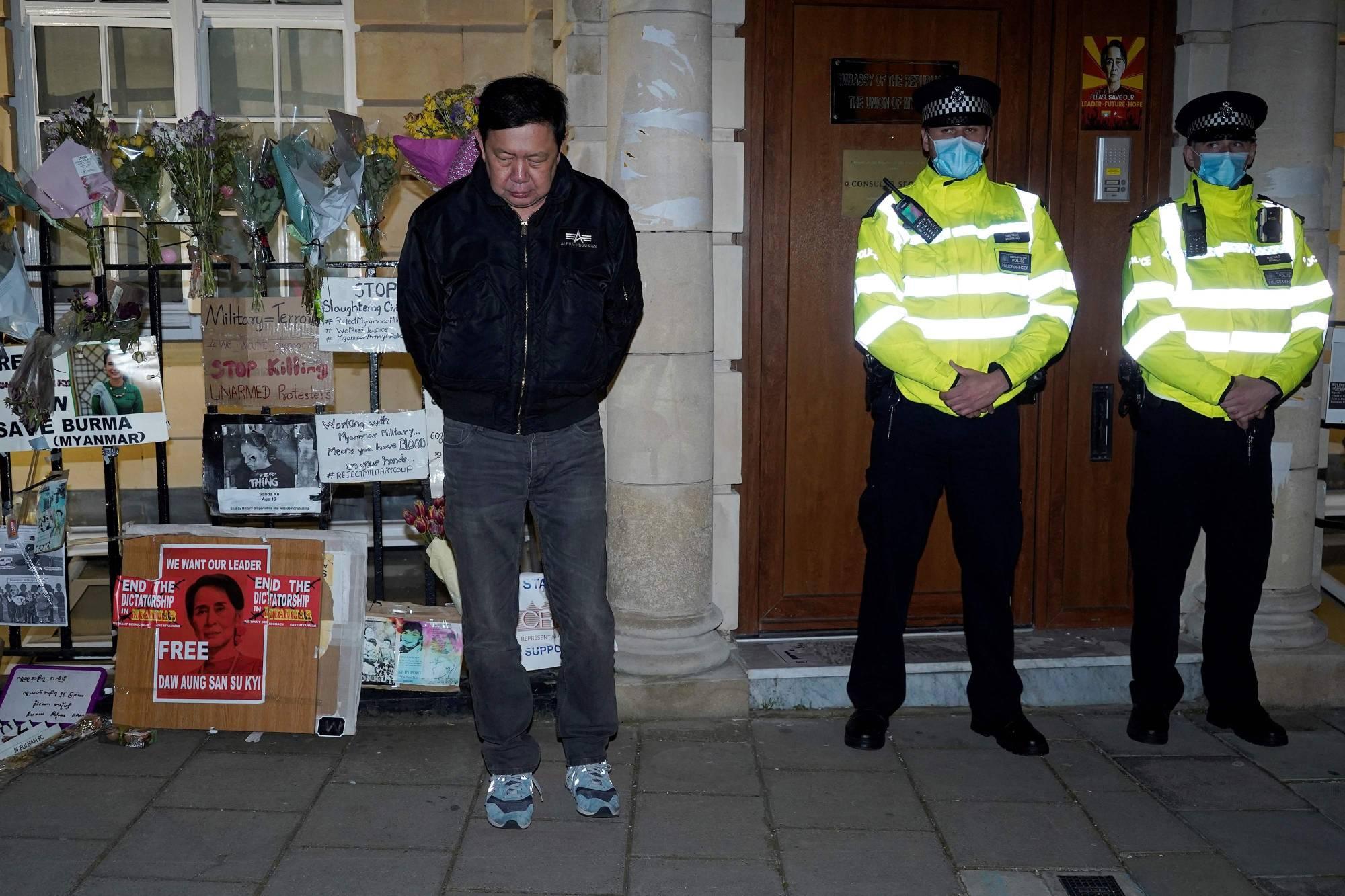 位于伦敦的缅甸驻英大使馆周遭目前有警员在场戒备,觉扎敏(左)在大使馆外不得其门而入。-法新社-