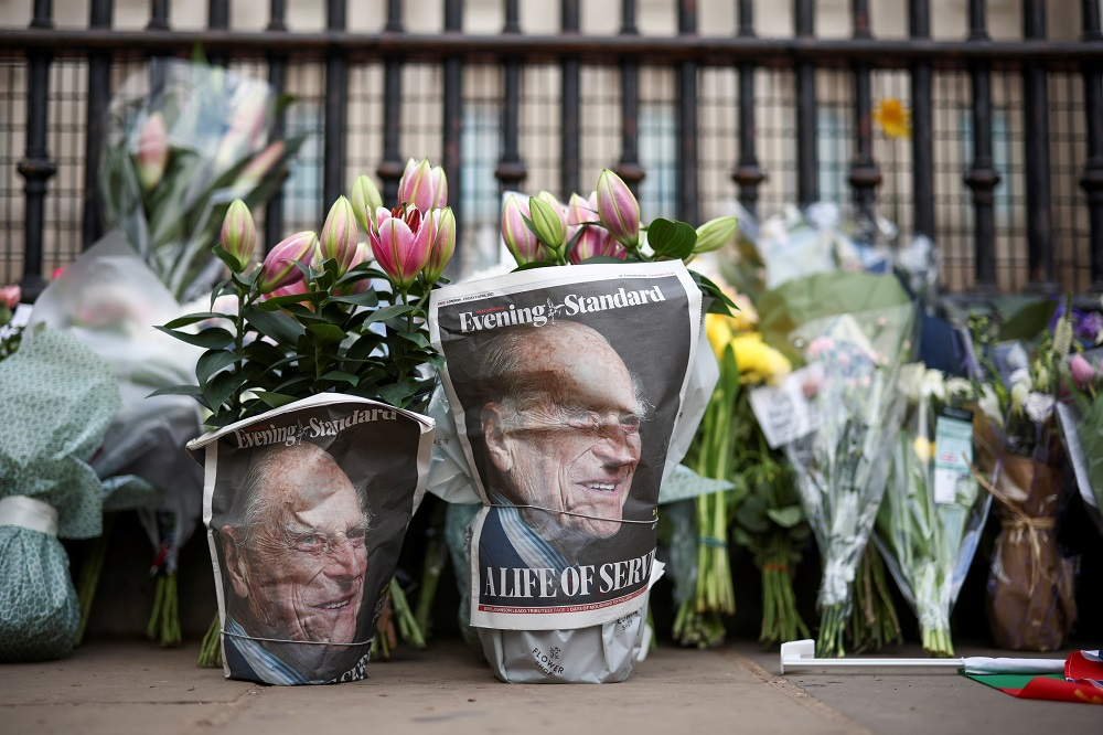 A picture of Britain's Prince Philip, husband of Queen Elizabeth, is seen in the newspapers wrapped around flowers, after he died at the age of 99, in London April 9, 2021. — Reuters pic