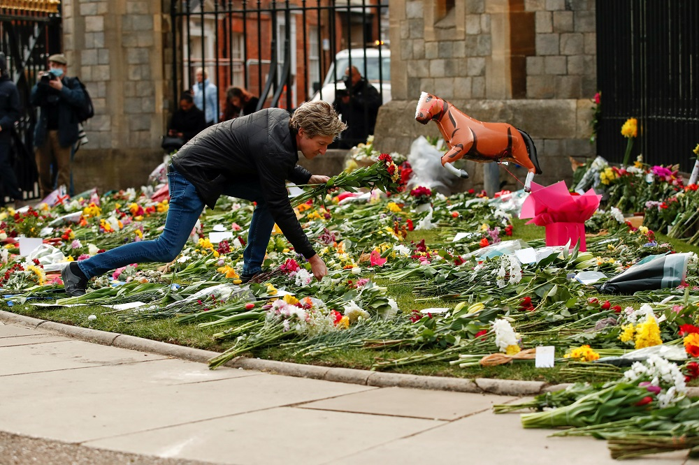 A person leaves flowers outside Windsor Castle after Britain's Prince Philip, husband of Queen Elizabeth, died at the age of 99, in Windsor, near London April 9, 2021. — Reuters pic