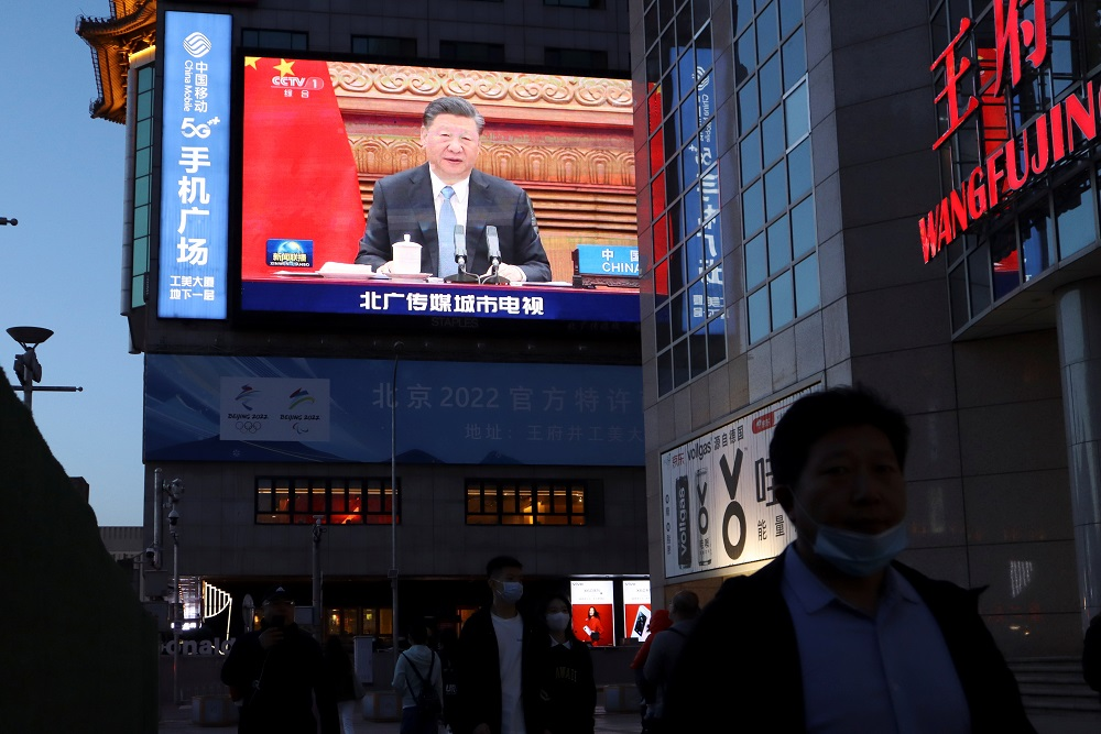 A giant screen shows news footage of Chinese President Xi Jinping attending a video summit on climate change with German Chancellor Angela Merkel and French President Emmanuel Macron, at a shopping street in Beijing April 16, 2021. — Reuters pic