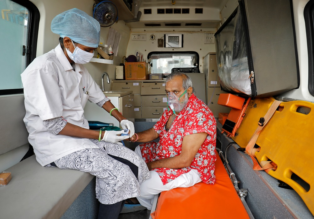 A paramedic uses an oximeter to check the oxygen level of a patient inside an ambulance while waiting to enter a Covid-19 hospital for treatment in Ahmedabad April 22, 2021. — Reuters pic