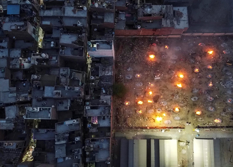 印度多个城市的火葬场都出现了遗体积压的情况,连火化场地和使用的木柴都出现短缺。图示新德里民众在居民区外焚烧尸体。-路透社-