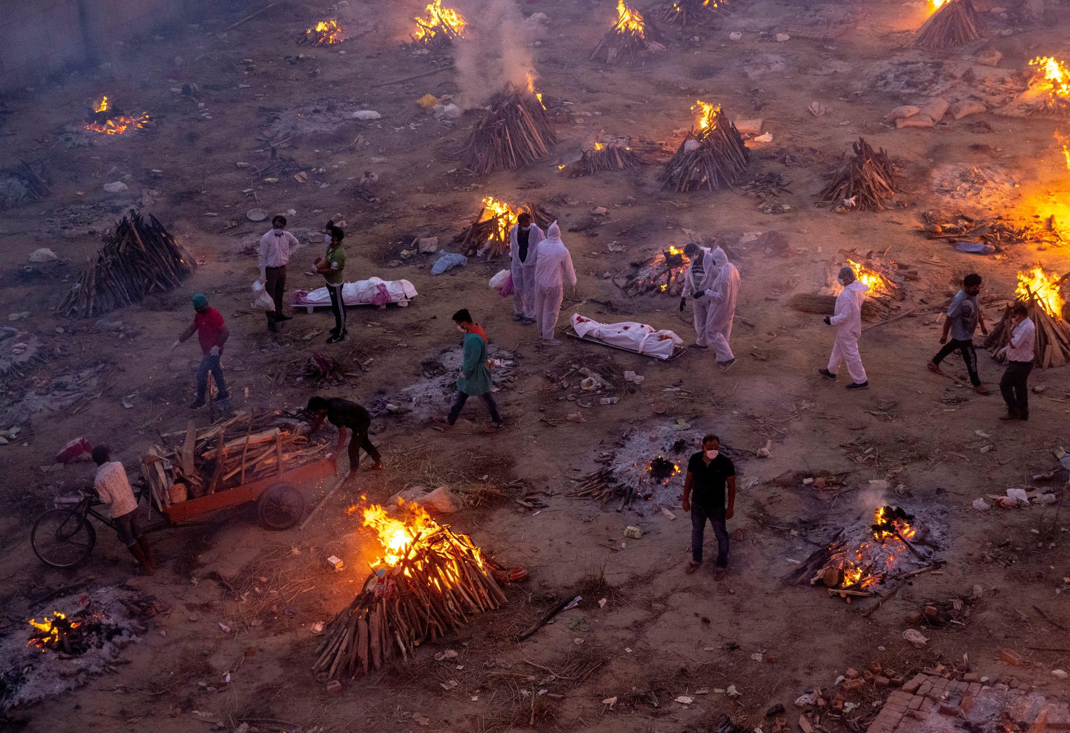 火葬场不够用,公园里、大街边、恒河河畔,到处都是焚烧尸体的火堆和埋尸的坑位。-路透社-