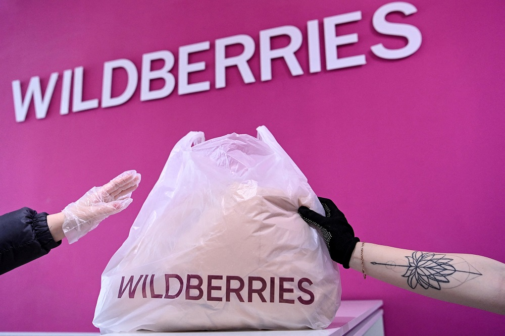 A woman receives her order at a pickup point of Russia's e-commerce giant Wildberries in Moscow. — AFP pic