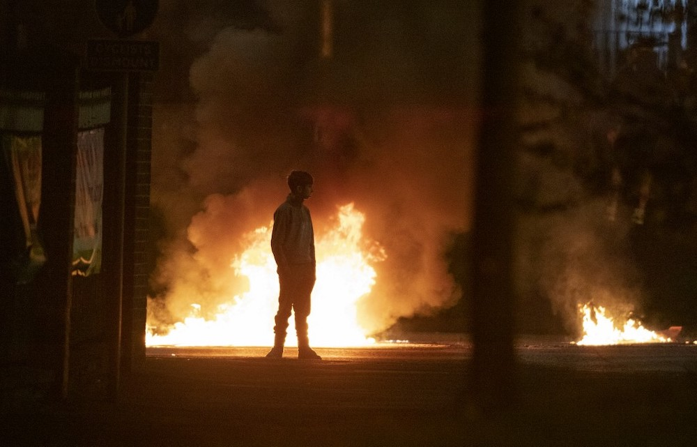 A boy stands and looks on as flames and smoke rises behind him in Northern Ireland on April 3, 2021. — AFP pic