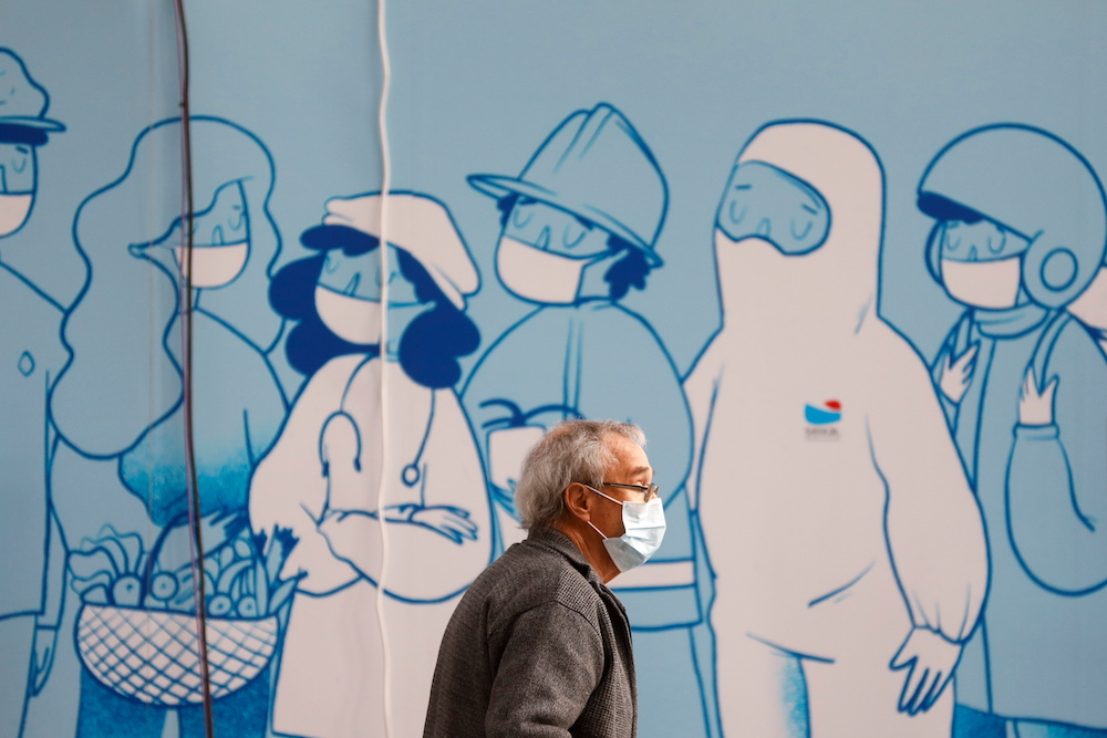 A man wearing a protective mask walks at a Covid-19 vaccination centre in Seixal, Portugal, March 22, 2021. — Reuters pic