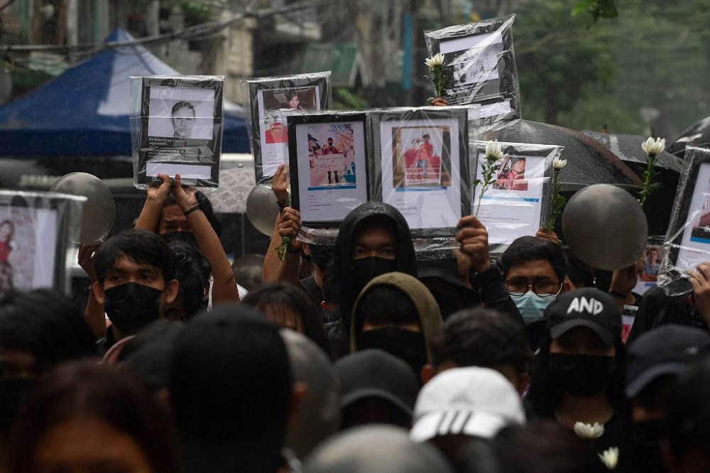 This photo taken and received from an anonymous source via Facebook April 5, 2021 shows protesters holding up portraits of people who have died while taking part in the demonstrations against the military coup, at a rally in Yangon. — Handout via AFP