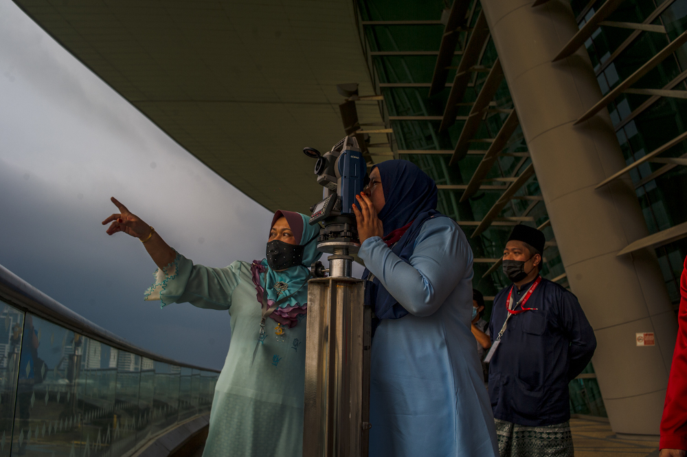 Officers from the Federal Territories Mufti Office look through a telescope to perform 'rukyah', also known as the sighting of the new moon for Ramadan, at the Putrajaya International Convention Centre April 12, 2021. — Picture by Shafwan Zaidon