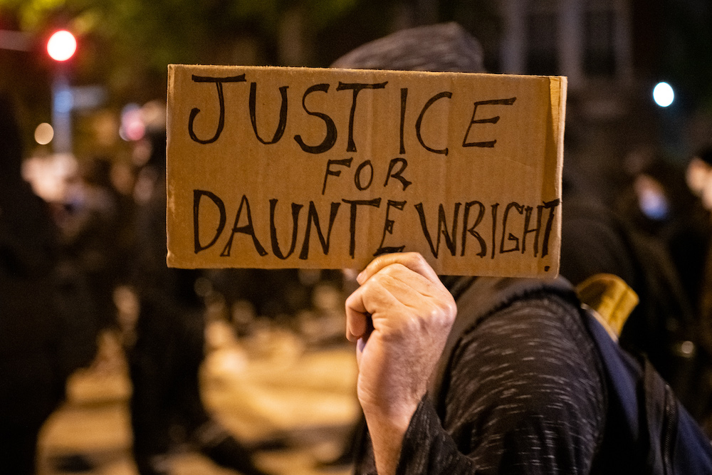 A demonstrator holds a sign that reads 'Justice for Daunte Wright' during a protest in Washington, D.C.,April 12, 2021. — Reuters pic